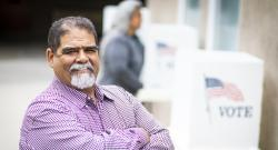 Smiling Latino man in front of voting booths