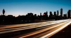 Blur of traffic light in front of backlit Manhattan skyline