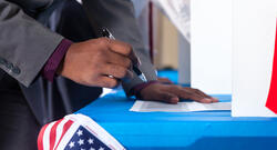 Black voter hovering over a former with a pen