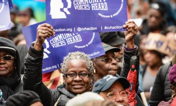 Woman holding poster above her head at Community Voices Heard rally