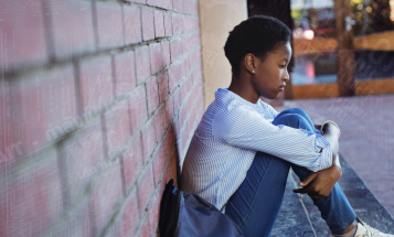 Black student sitting against brick wall with knees against chest