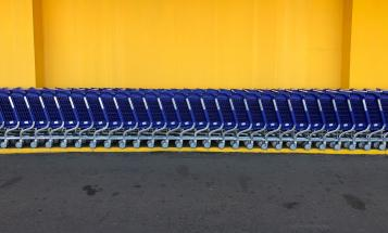 Blue grocery carts against yellow wall