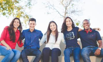 Group of smiling college students sitting outside on a bench