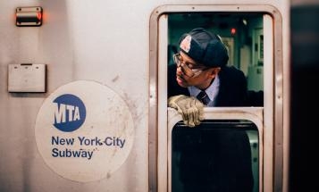 Black New York City Subway employee looking out train window