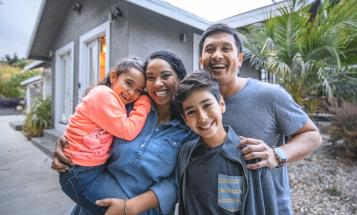 Smiling Latino family outside house