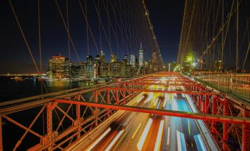 Blurred cars crossing New York City bridge at night
