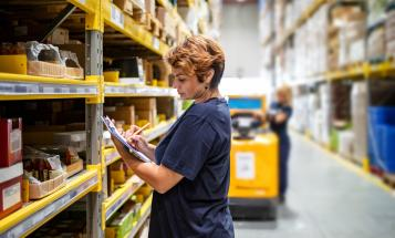 Woman warehouse worker holding clipboard, surveying inventory