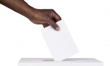 A dark-skinned hand is about to place a slip of paper in a white ballot box