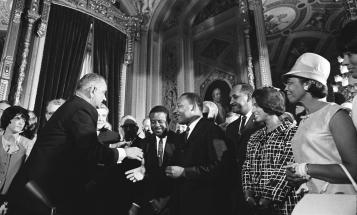 Lyndon Johnson shakes Martin Luther King, Jr.'s hand after signing the Voting Rights Act of 1965
