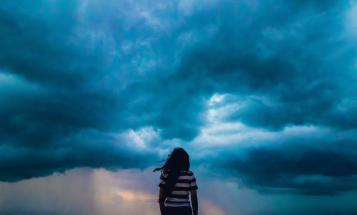 View of woman from behind as she looks out at incoming storm clouds