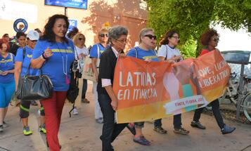 Latinas marching with a banner for love and liberation