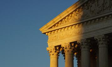 Supreme Court building cast half in light and half in shade from setting sun