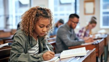 Black student in classroom, writing