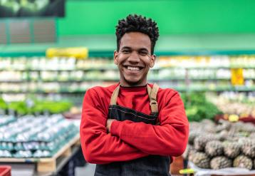 Smiling black retail worker in front of groceries