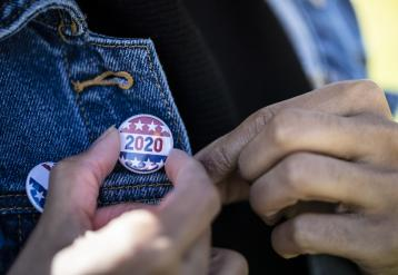 Black voter adjusting a 2020 flag pin on their jacket lapel
