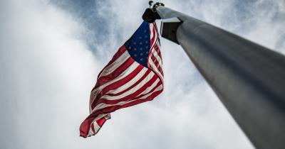 Looking up a flagpole at the U.S. flag