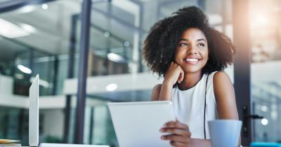 Black woman smiling and looking out window with laptop