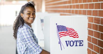 Young smiling voter at voting booth