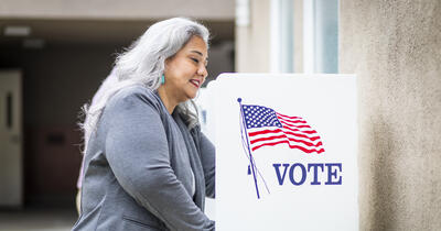 Latina woman voting at a voting booth
