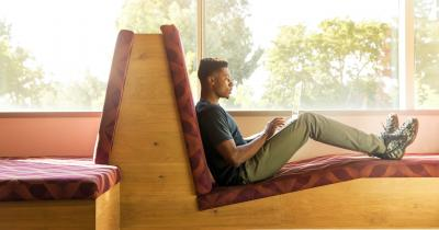 Black student reclined and working on computer