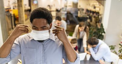Black worker putting on mask with people waiting in the background