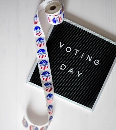 I Voted sticker roll over Voting Day sign