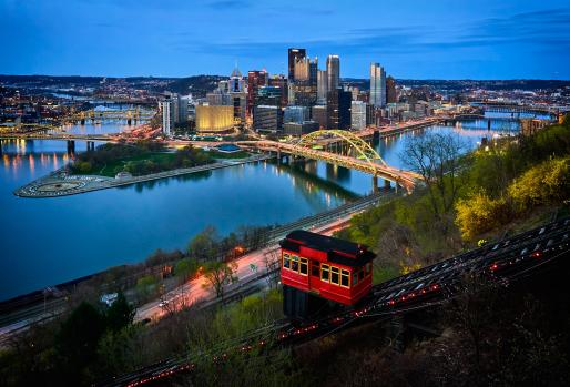 Pittsburgh skyline at dusk from hillside overlooking river